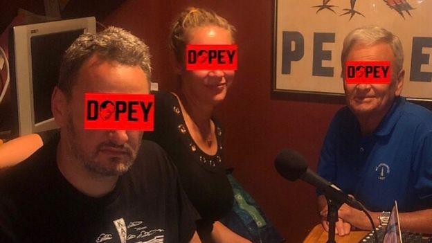 Dave, Linda e Alan sentados na mesa da cozinha, diante do microfone, gravando episódio recente do podcast Dopey