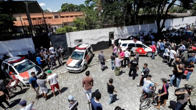 Police stand guard at a school after a shooting as people gather, in the metropolitan region of Sao Paulo, Brazil, 13 March 2019