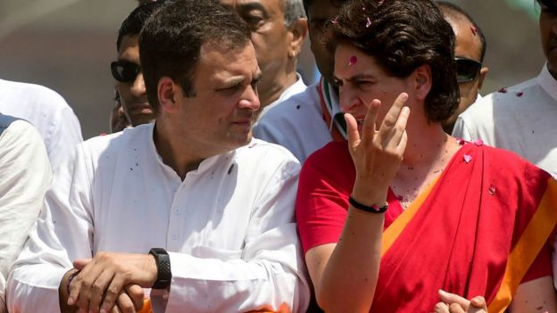 Indian National Congress party president Rahul Gandhi (L) and his sister Priyanka Gandhi (R) wave during a roadshow before filing his nomination for the upcoming general election at the district collector's office in Amethi on April 10, 2019.