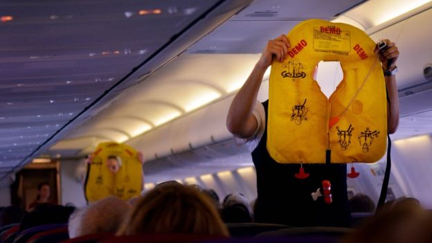 Comissários de bordo orientam sobre coletes salva-vidas