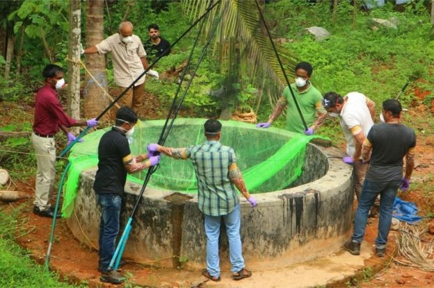 Animal Husbandry department and Forest officials inspect a well to to catch bats at Changaroth in Kozhikode in the Indian state of Kerala on May 21, 2018.