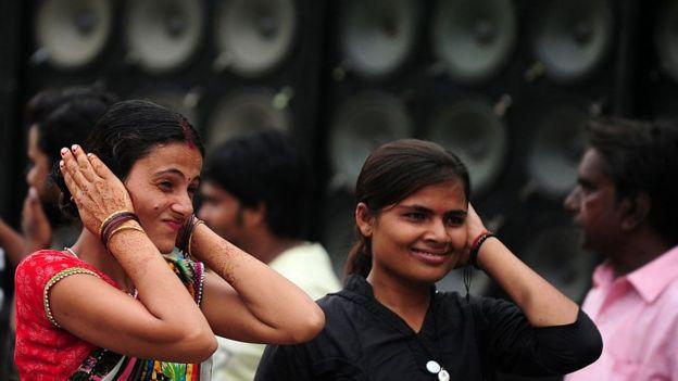 Mujeres se tapan los oídos.