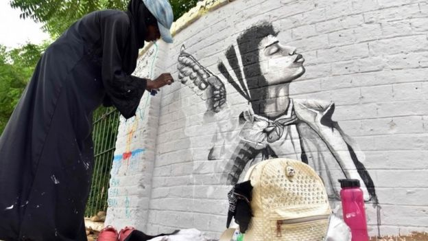 A Sudanese artist paints a mural on a wall in the capital Khartoum on 22 August 2019