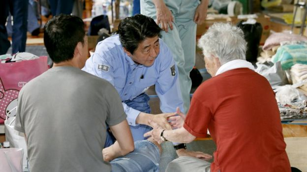 Japanese Prime Minister Shinzo Abe (C) visits evacuated residents