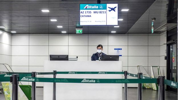 airport worker in italy wearing a mask