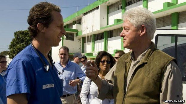 UN Special Envoy to Haiti former US President Bill Clinton speaks to a doctor at the General Hospital in downtown Haiti