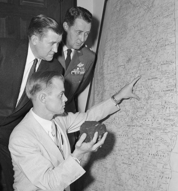 El abogado de Ann Hodges sostiene el meteorito mientras apunta en un mapa al pueblo de Sylacauga, donde cayó la roca espacial.
