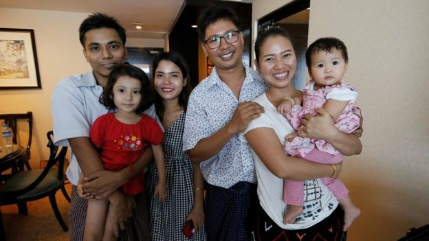 Wa Lone poses with wife Pan Ei Mon and daughter, along with Reuters reporter Kyaw Soe Oo carrying his daughter next to wife Chit Su Win,