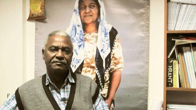 Bir fotoğraf önünde oturan Afrika kökenli adam