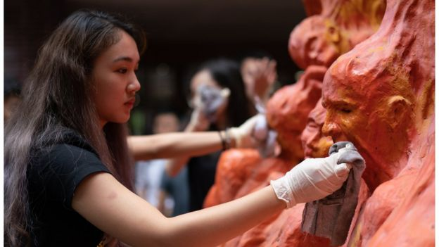 "Students clean the ""Pillar of Shame"" statue, an art piece dedicated to the victims of the 1989 Beijing Tiananmen Square massacre,"