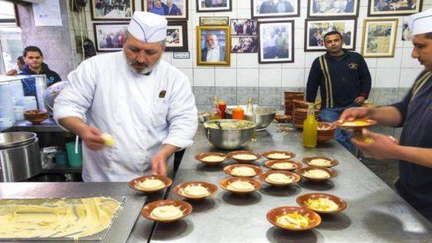 Cocineros preparando humus.