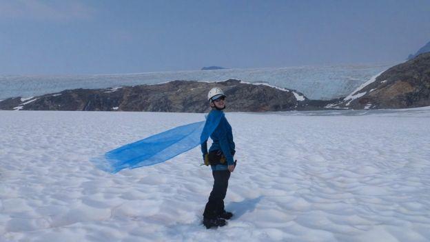 Celeste Labedz posa junto a su capa en el glaciar