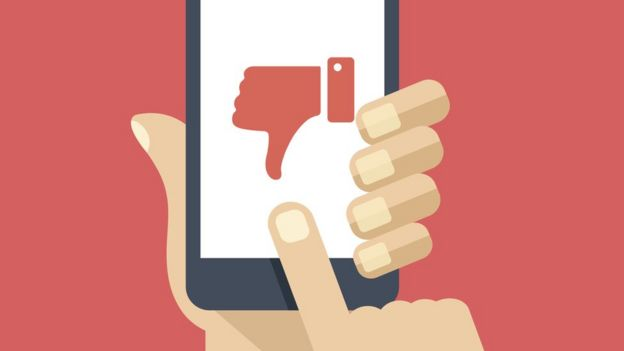 Ilustração de uma mão segurando um celular - na tela, há um símbolo de uma mão com o polegar para baixo