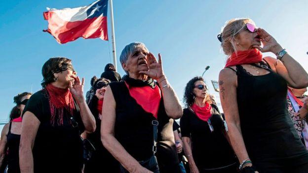 """Mujeres protestando con la coreografía """"Un violador en tu camino"""" en Santiago"""