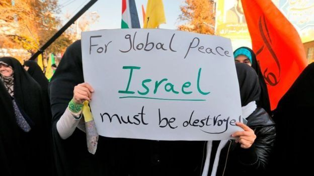 "Protesters with a banner that says: ""For global peace, Israel must be destroyed"""