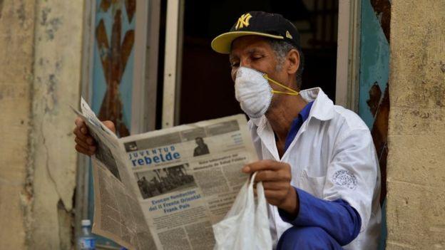 Hombre con máscara lee un diario en La Habana