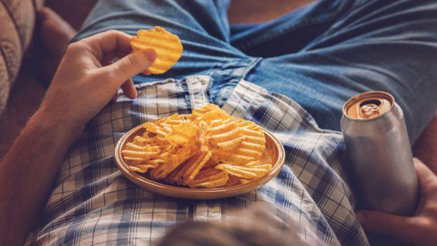Un hombre comiendo papas fritas y tomando un refresco.