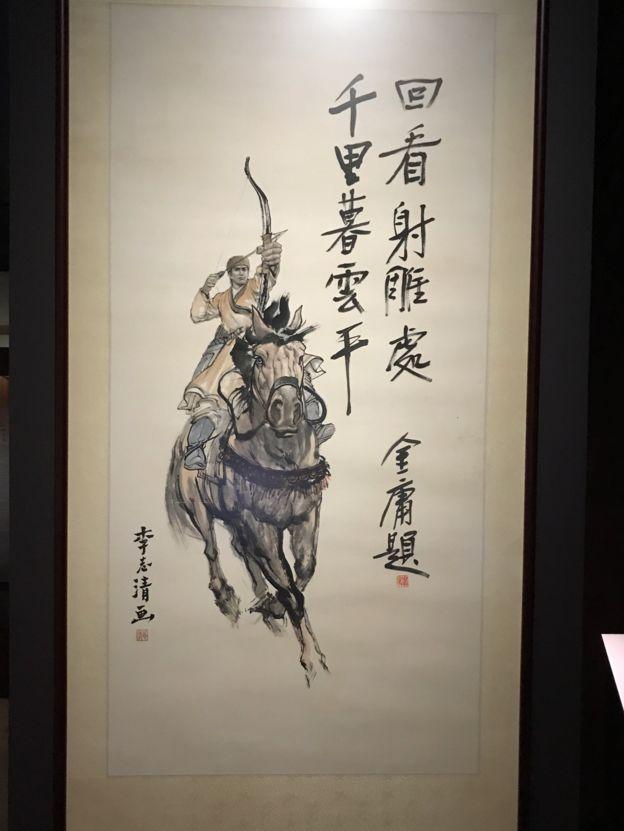 ลายมือเขียนของกิมย้ง ประกอบกับภาพนักบู๊บนหลังม้าน้าวคันธนู