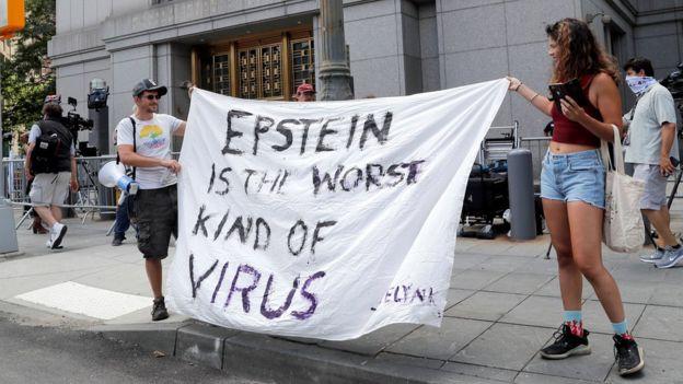 """Un hombre y una mujer sujetan un cartel que dice: """"Epstein es el peor tipo de virus""""."""