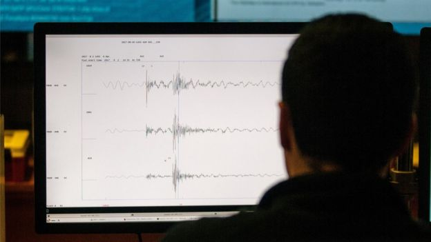 Un hombre mira una computadora en la que se ven ondas sísmicas