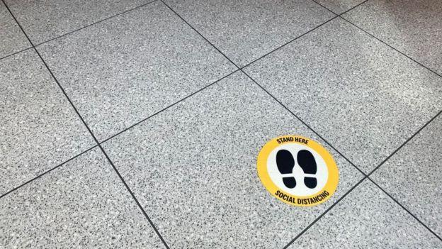 """Un cartel en el piso lee: """"Párate aquí"""""""