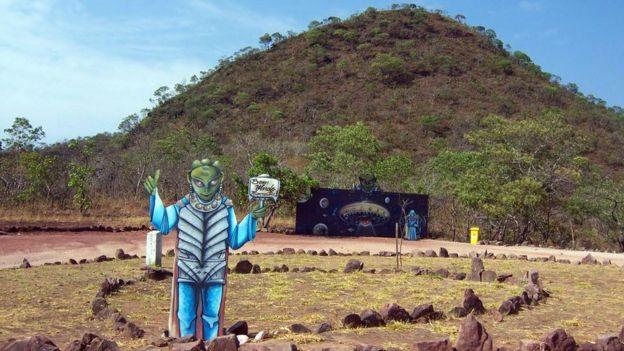 Localizado em uma área rural, o discoporto conta com um painel ilustrativo e uma imagem de um alienígena verde com uma placa 'bem-vindo'