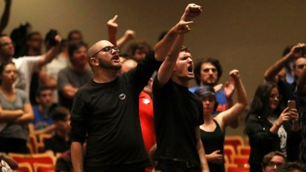 Members of a crowd at white nationalist Richard Spencer's speech at University of Florida raise fists and chanted in Gainesville, Florida.