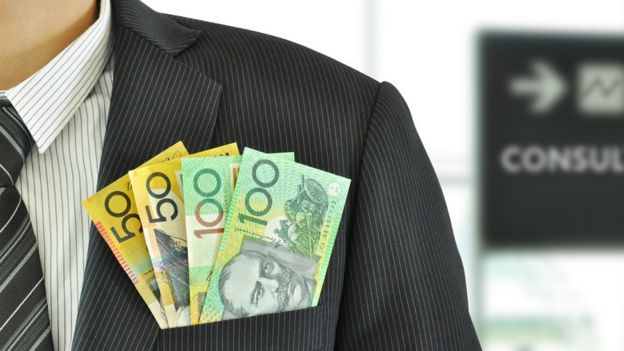 Australian money sticking out of the pocket of a man wearing a suit