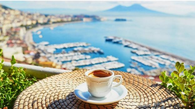 Una mesa y un café, con vista a la bahía de Nápoles