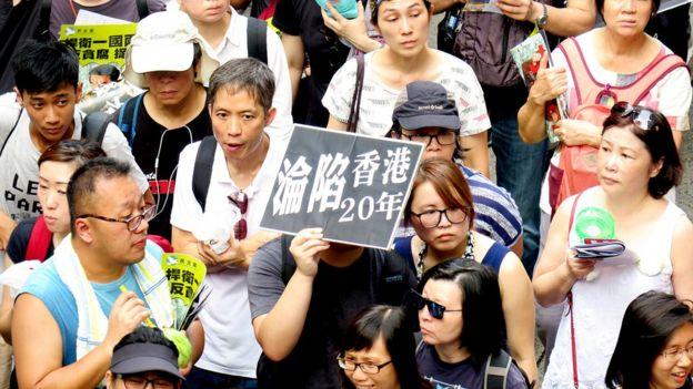 """香港七一游行队列中一名示威者举起""""香港沦陷20年""""标语牌(1/7/2017)"""