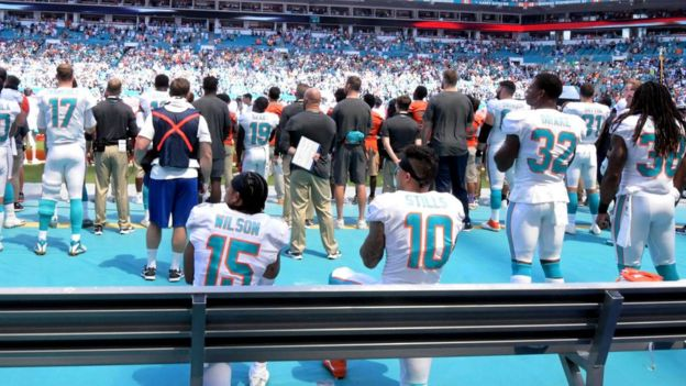 Miami Dolphins players kneeling during the national anthem
