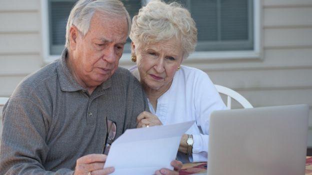 Casal de idosos olham papeis