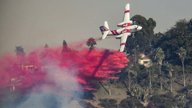 Una avioneta sobrevuela el lujoso barrio de Bel Air, en Los Ángeles, California, para extinguir el incendio Skirball