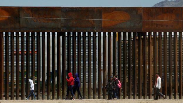 Migrants walk along the border fence after crossing illegally into El Paso, Texas