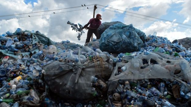 A man stands on top of a pile of plastic rubbish