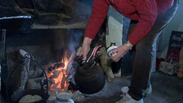 Margaret Gallagher cooks over an open fire