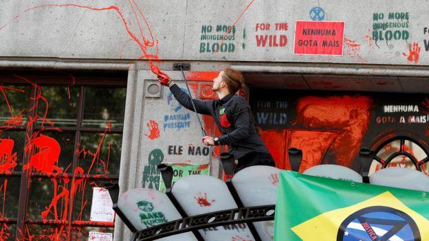 Um ativista joga tinta vermelha na fachada da Embaixada brasileira durante um protesto do Extinction Rebellion na Embaixada brasileira em Londres em 13 de agosto de 2019