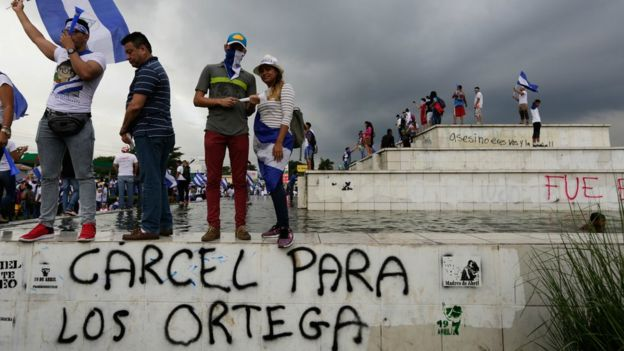 "Demonstrators stand above graffiti reading ""Jail for the Ortegas"" in Managua on May 26, 2018"