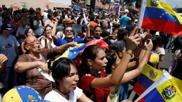 Dad ku dhawaaqaya hadallo ka dhan ah madaxweyne Maduro iyaga oo ag maraya meel codka laga dhiibanayo oo ku taalla Caracas