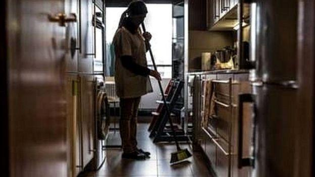 Mujer limpia la cocina de una casa.