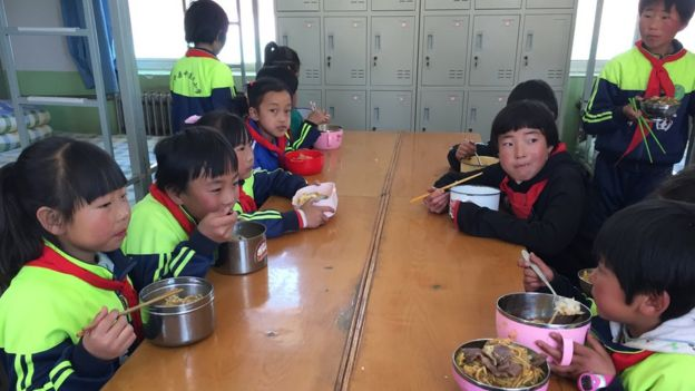 Kids at the school sit around a table eating food