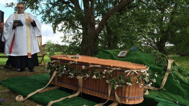 Un ataúd de mimbre siendo enterrado en un bosque.