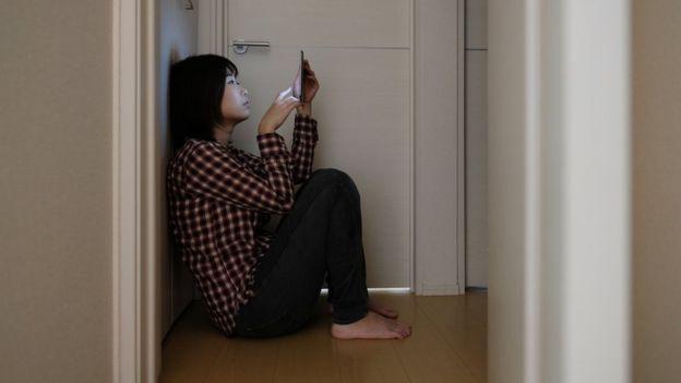 joven japonesa usando celular en un cuarto