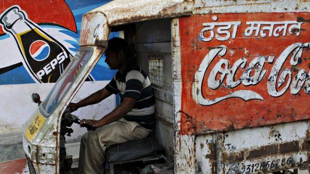 Carrito de Coca-Cola pasando frente a mural de Pepsi