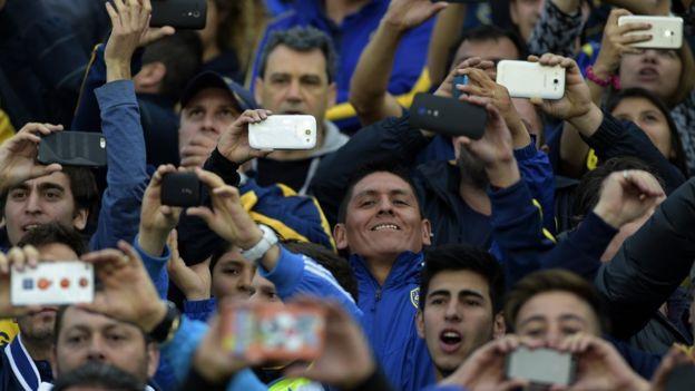 Aficionados usan sus teléfonos en el fútbol