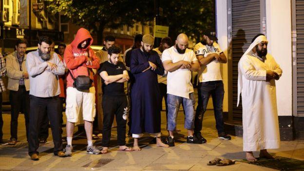 Gente rezando tras el incidente en Finsbury Park.