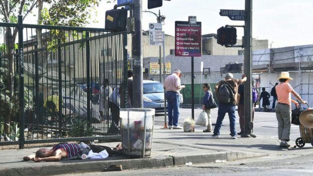 Un indigente está acostado en una acera en Los Ángeles