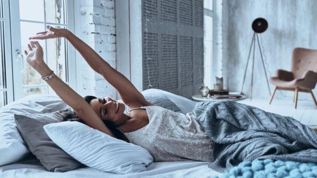 Imagem mostra mulher acordando com um sorriso, em um quarto
