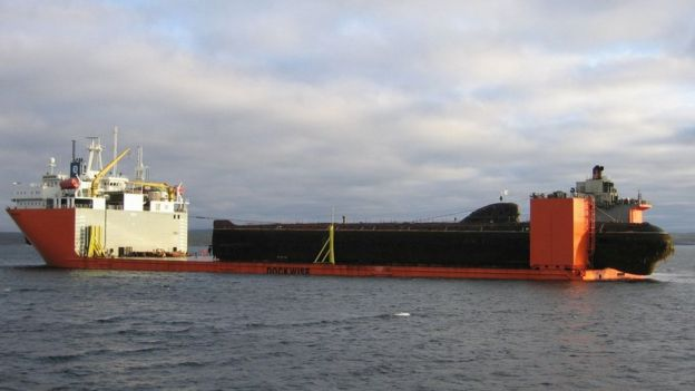 Barco carga un submarino.