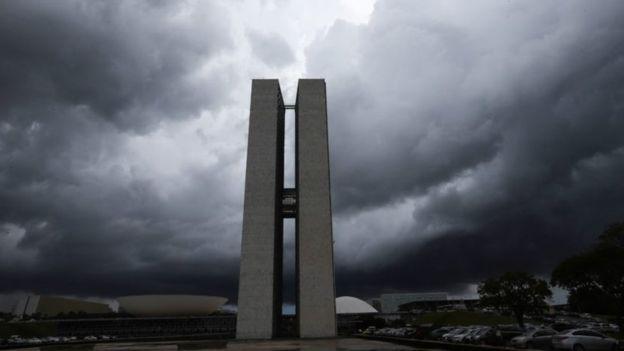 Prédio do Congresso Nacional rodeado por nuvens carregadas